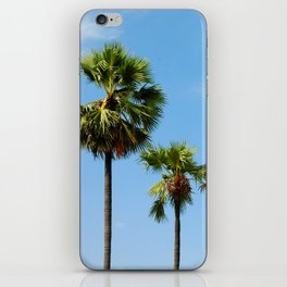 Coconut trees against a blue sky iPhone Skin