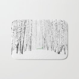 Green bench in white winter forest Bath Mat