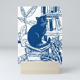Sitting on a pile of books Mini Art Print