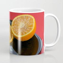 Sliced orange on the black plate and red background Coffee Mug