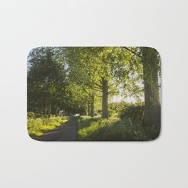 sunset through avenue of Poplar trees along a country road Bath Mat
