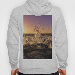 Magical sunset and waves breaking over rocky beach Hoody