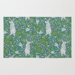 Grey hares with coltsfoots and snowdrops on green background Rug