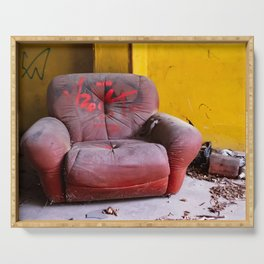 old red armchair abandoned in a disused warehouse Serving Tray