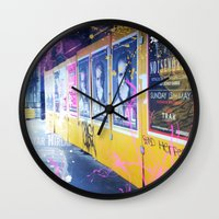 alisa burke Wall Clocks featuring purple and yellow _  little burke graffiti by Vin Zzep