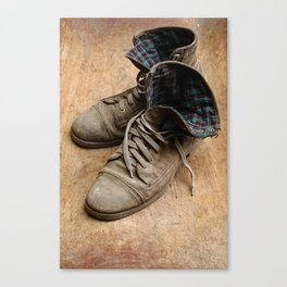 Pair of old leather shoes, worn-out and dusty, on wooden background Canvas Print