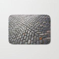 Leaves on cobblestones Bath Mat
