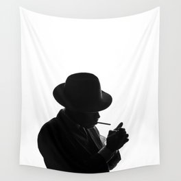 Silhouette of private detective in old fashion hat lights a cigarette Wall Tapestry