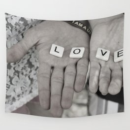 Love- a couple holding tiles spelling Wall Tapestry