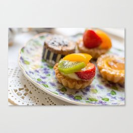 Small fruit tarts laid out on an antique china plate Canvas Print