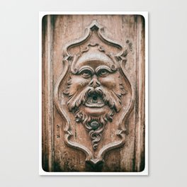 Face with beard carved on ancient door in Pisa Tuscany Italy Canvas Print