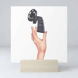 A hand drawn hand with red nail polish holding a movie film collage Mini Art Print