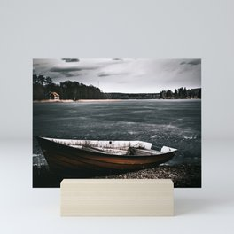 Boat on frozen shore Mini Art Print