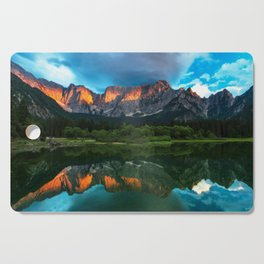 Burning sunset over the mountains at lake Fusine, Italy Cutting Board