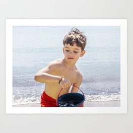 Young boy playing on a beach in French Riviera Art Print