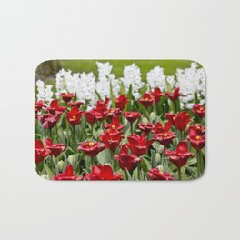 Red Tulip Field with White Hyacinth Flowers Blooming in the Background in Amsterdam, Netherlands Bath Mat