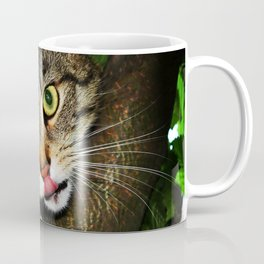 Cat licking nose hunting prey extending claws sitting on tree predator cat Coffee Mug