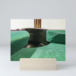 Hole of a billiard table with green cloth and on the background the billiard cues Mini Art Print
