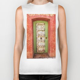White and green wooden door with red wall in a typical village in Provence France Biker Tank