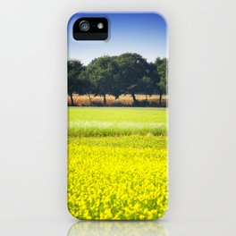 Mustard seed field with a row of trees and maize iPhone Case