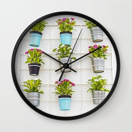 Colorful flower pots hanging from a white wall Wall Clock