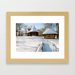 Snow cover in a Romanian Village with an old wooden church Framed Art Print
