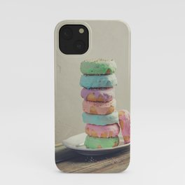 A stack of donuts on wooden table against the wall iPhone Case