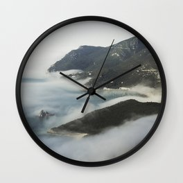 Misty ocean by the mountains Wall Clock