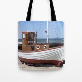 Wooden fishing boat on the beach. Tote Bag
