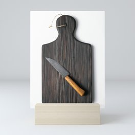 Cutting board with a knife on a white background Mini Art Print