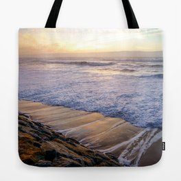 White waves crashing into mossy rocks, with a beautiful autumn sunset. Tote Bag