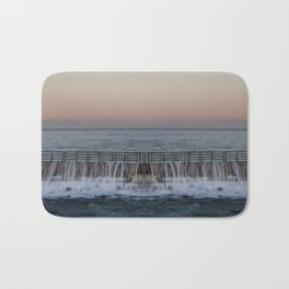 A reflected panorama of a seawall as a wave washes over it in La Jolla, San Diego, California Bath Mat