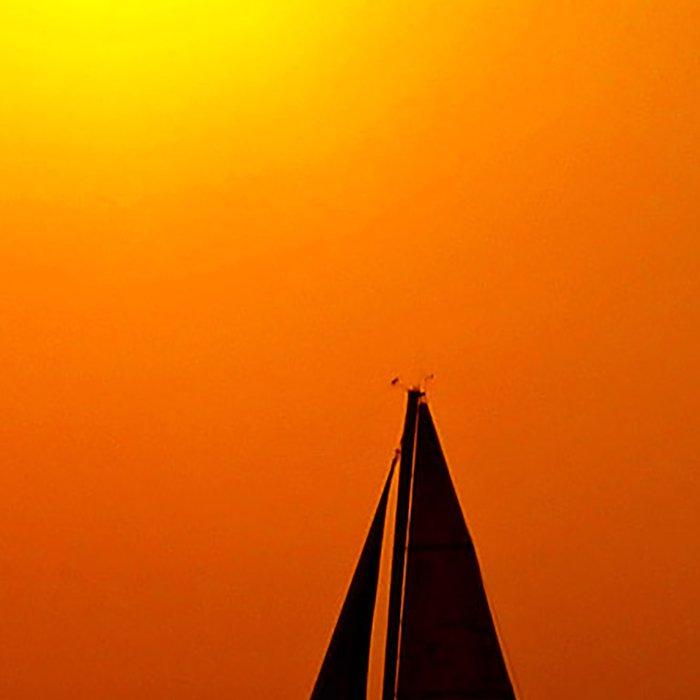A sailboat at sunset Leggings