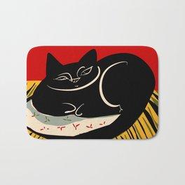 Black cat on a striped cushion Bath Mat