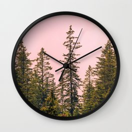 Tall trees against pink sky Wall Clock