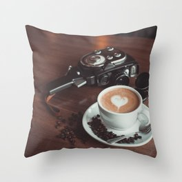 A cup of hot cappuccino placed on a table next to the old camera with lens and coffee beans Throw Pillow