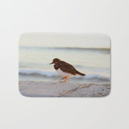 Sandpiper bird enjoying some relaxing time by the sea Bath Mat