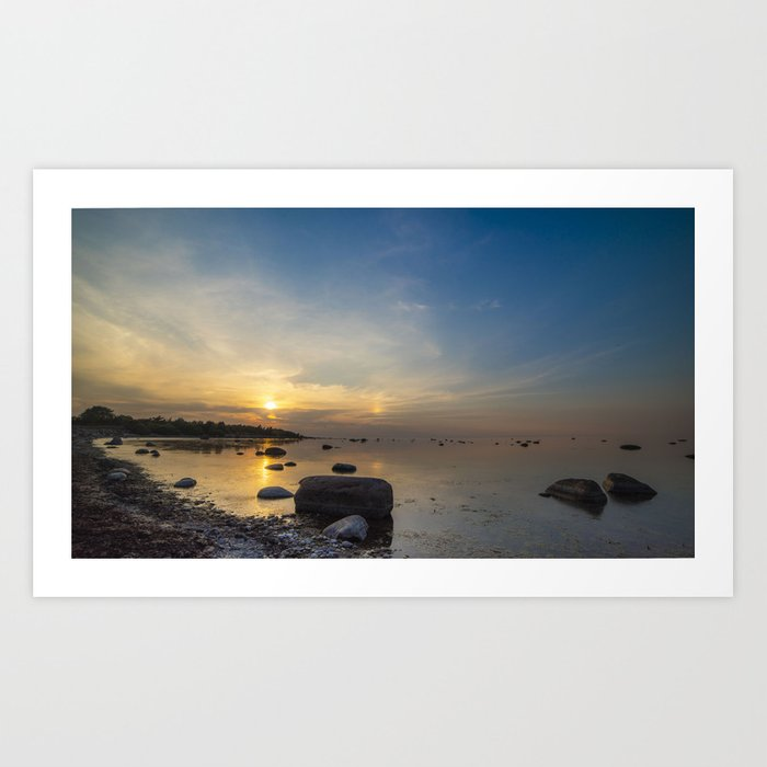 Sun with faint halo over the calm sea and reef rocks Kunstdrucke