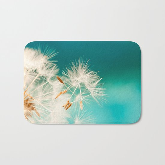 dandelion seeds blowing in turquoise Bath Mat