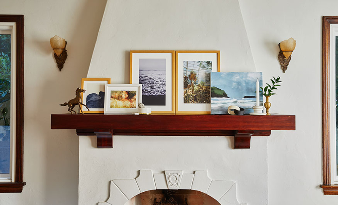 framed prints and canvas prints sitting on mantel