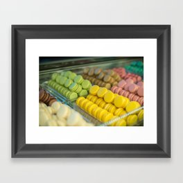 Colourful tasty macaroons in a row in the sweet shop Framed Art Print