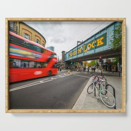 Long exposure of the painted Camden Lock bridge across Camden High Street with a blurred red London Double Decker bus approaching Serving Tray