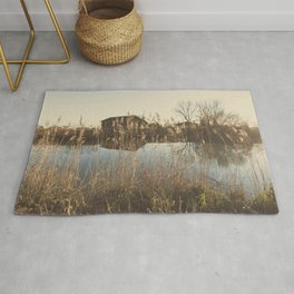 A cottage along a river Rug