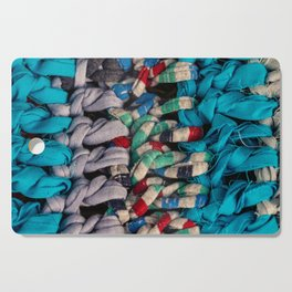 Rustic fabric made with recycled fabrics. Colorful handmade fabric. Vibrant colors of a fabric detai Cutting Board