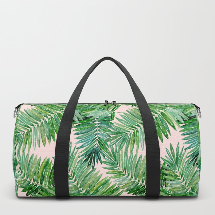 Green palm leaves on a light pink background. Duffle Bag