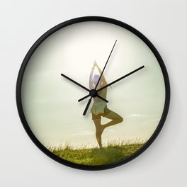 Yoga tree pose on a hill Wall Clock