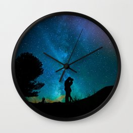Silhouettes of a loving couple against a starry sky Wall Clock