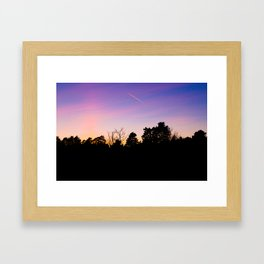 Black silhouette of trees in a forest against vibrant pink purple sunset sky with jetstream Framed Art Print