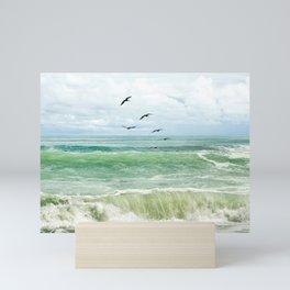 Birds flying above ocean Mini Art Print