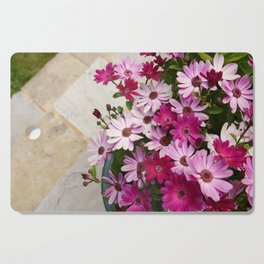 Flower pot full of African daisies Cutting Board